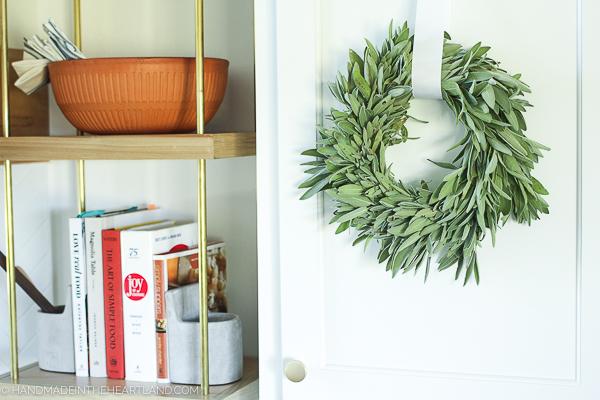 Fresh sage wreath hanging on cabinet in kitchen