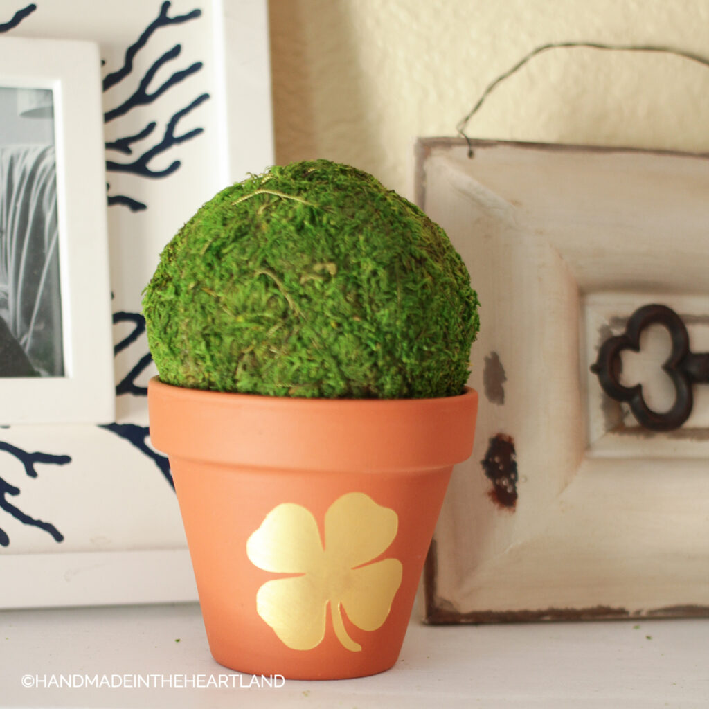 gold four leaf clover painted on terra cotta flower pot