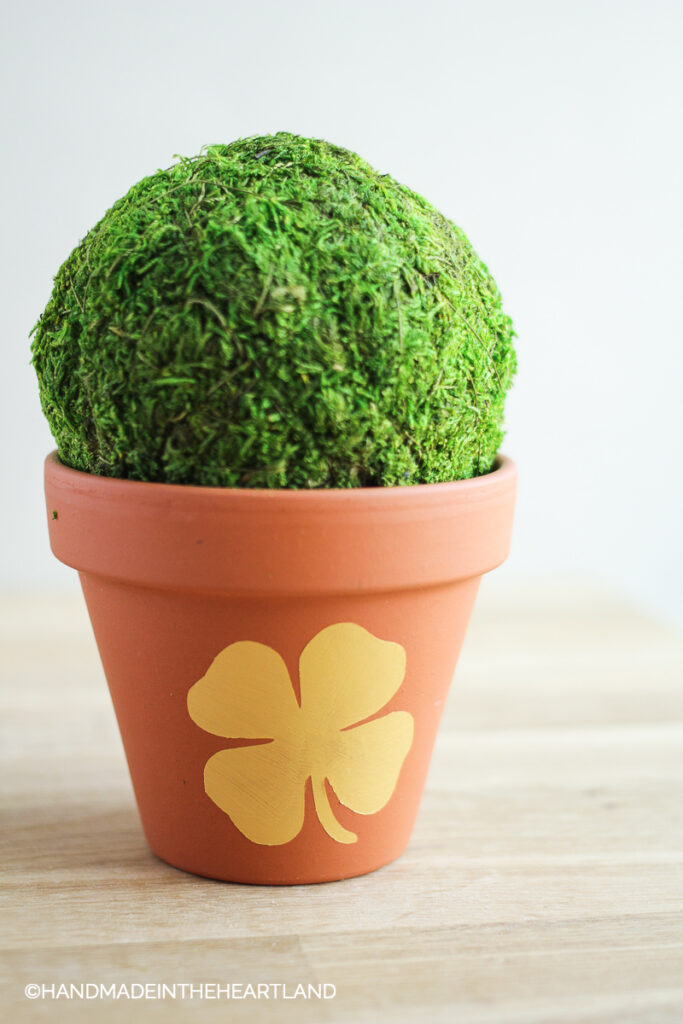terracotta flower pot with painted four leaf clover with topiary green ball in it