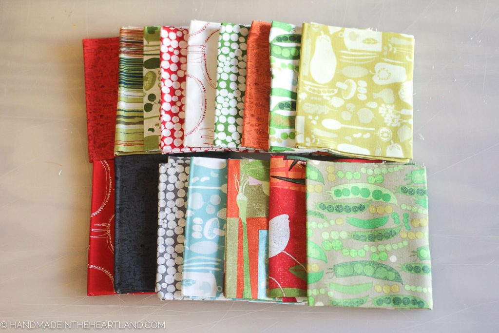 a picture of 16 different fabrics folded on a table.