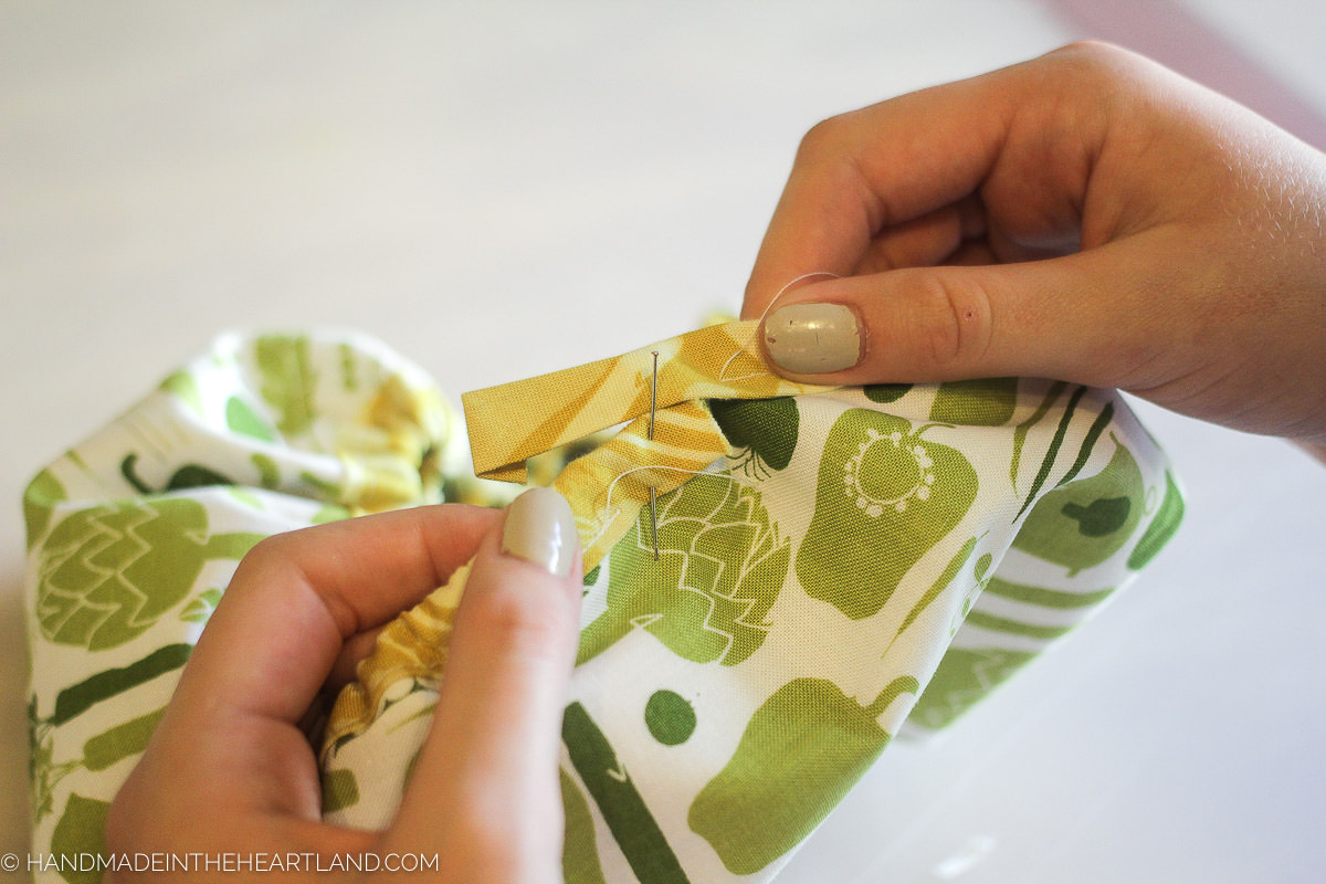 pinning the bias tape at the end to close the mixing bowl cover