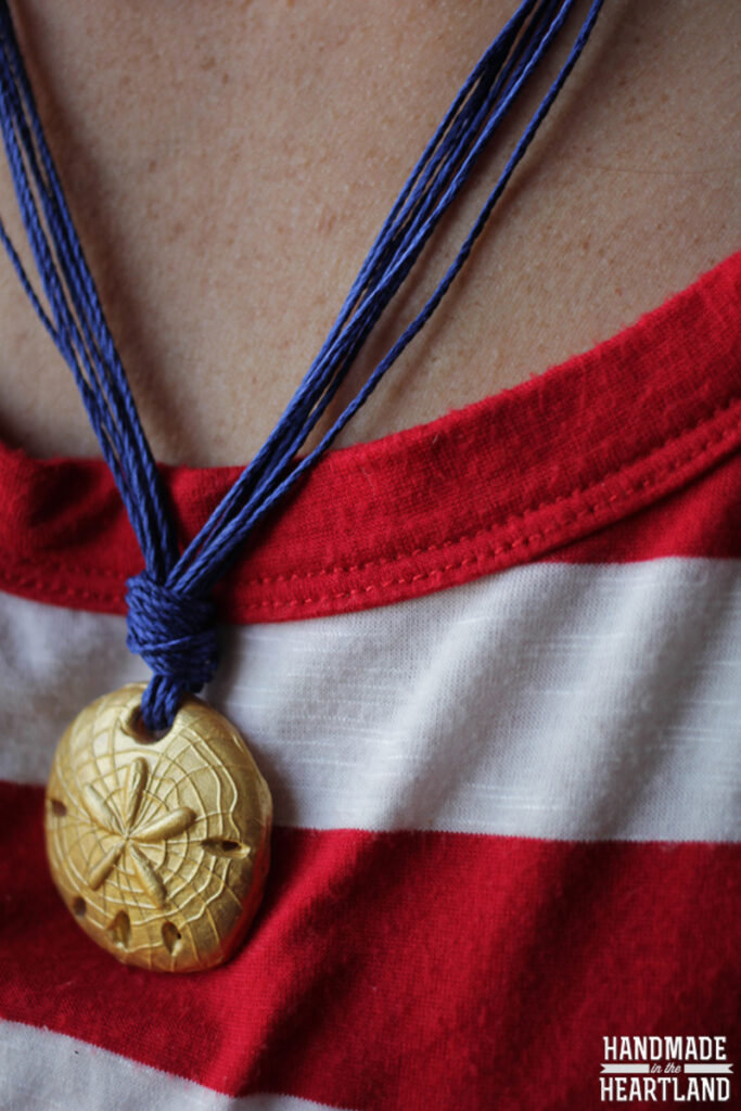 gold sand dollar polymer clay bead on blue string necklace