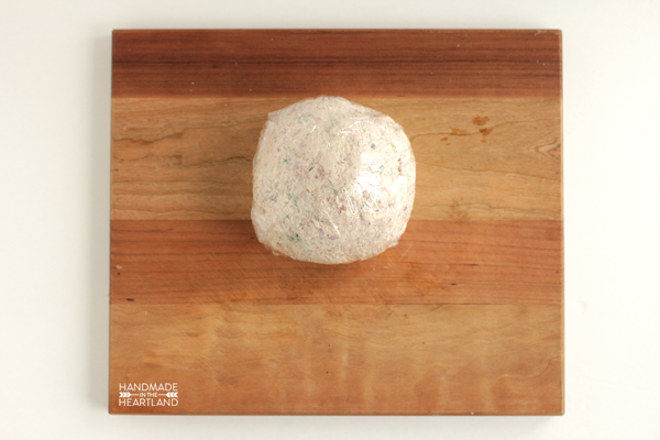 corned beef cheese ball wrapped in plastic wrap sitting on cutting board