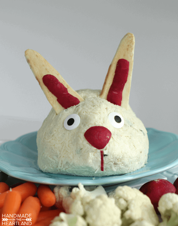 Cheeseball decorated to look like an Easter bunny sitting on a blue plate with vegetables around it