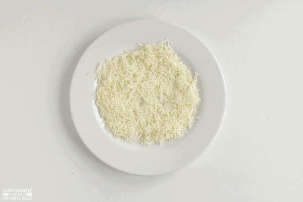 shredded cheese on a white plate ready to roll a cheeseball into