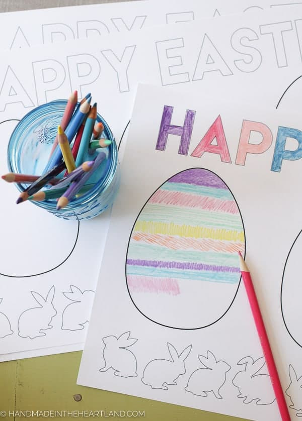 Easter egg coloring page on table with jar of colored pencils