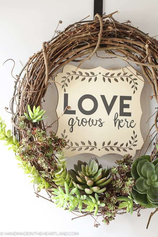 "grapevine wreath with faux succulents on the bottom and ""love grows here"" on a wood piece in center"
