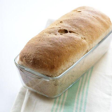 whole wheat bread in a glass bread pan