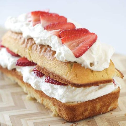 A pound cake loaf, cut in half lengthwise with strawberries and whipped cream in the center and on top