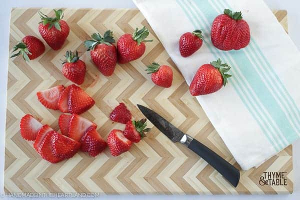 Strawberries being cut on a Thyme and Table chevron cutting board