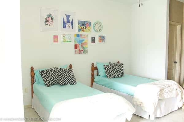 Modern kids room decor refresh after shot- showing 2 twin beds with aqua bedding and white walls with white framed kids artwork