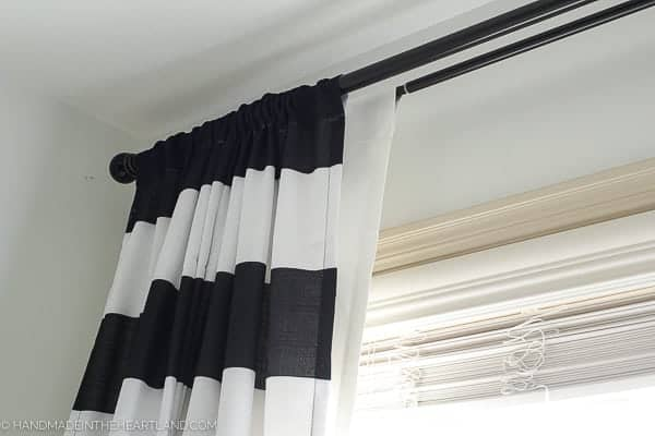 black and white striped curtains in front of blackout curtains in a modern kids room