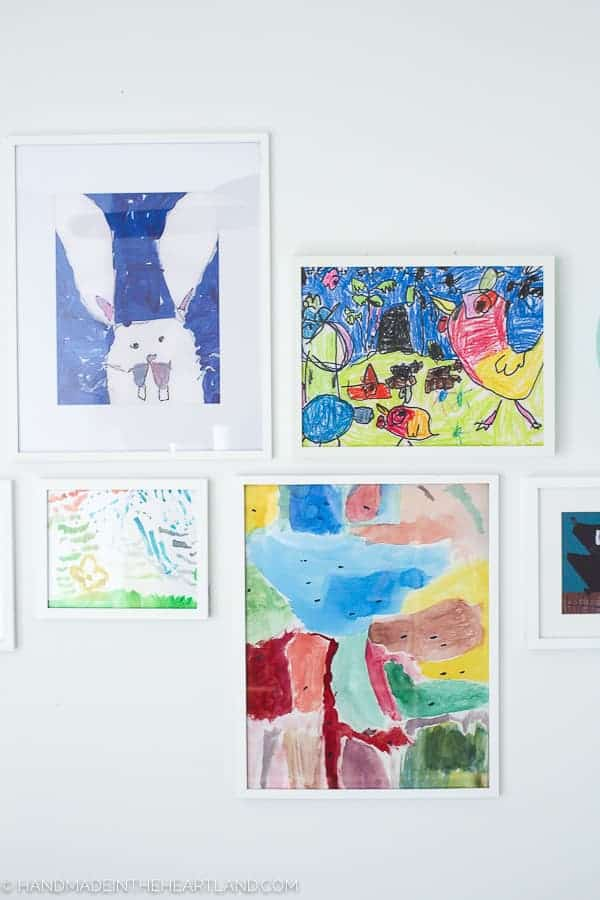 kids artwork displayed in simple white frames on a white wall