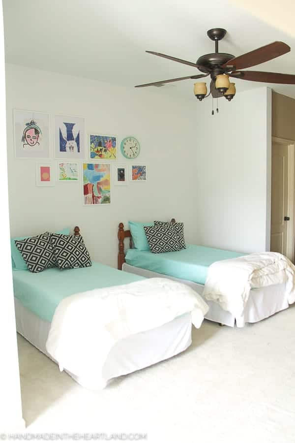modern kids room with aqua bedding, black and white pillows and white framed kids artwork on the wall