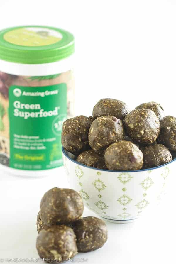 Energy bite balls in a bowl with amazing grass container in background
