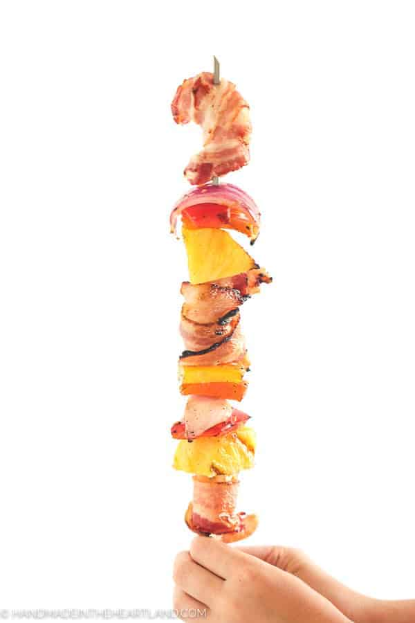 Image of kabob sticks with bacon wrapped shrimp and veggies.