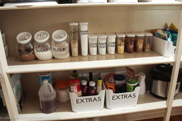 Image of nicely labeled clear containers with pantry staples such as corn starch, flour and oats.
