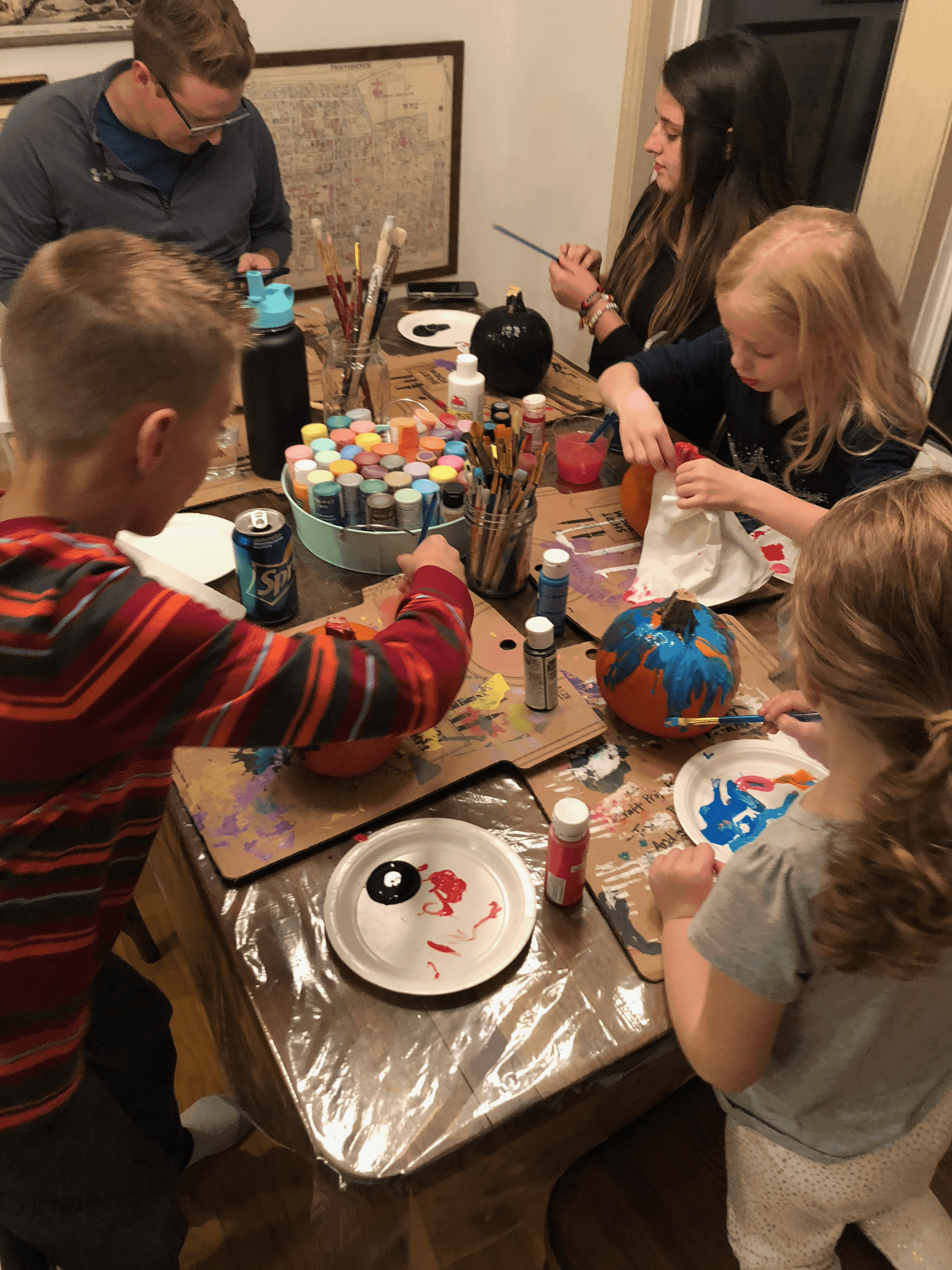 family gathered around kitchen table painting pumpkins