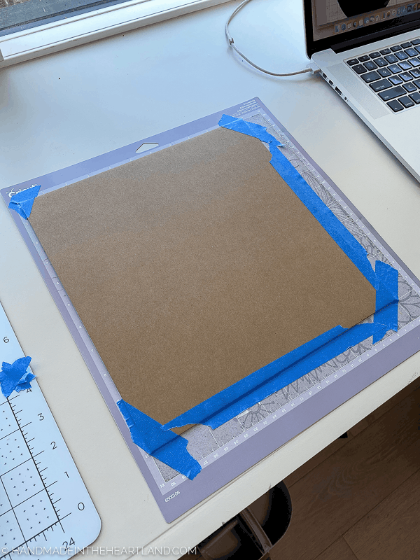 chipboard prepared on Cricut cutting mat with painters tape
