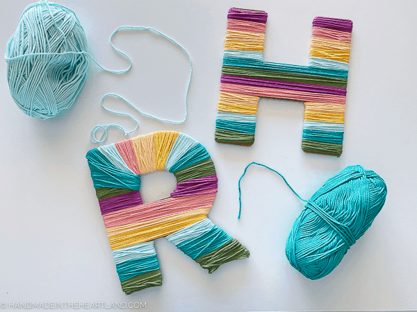 Chipboard cut letters wrapped in rainbow colored yarn stripes