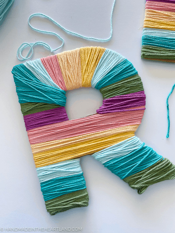 Yarn wrapped letter in modern rainbow colors, made with the Cricut Maker, Cricut Chipboard and Cricut Knife Blade