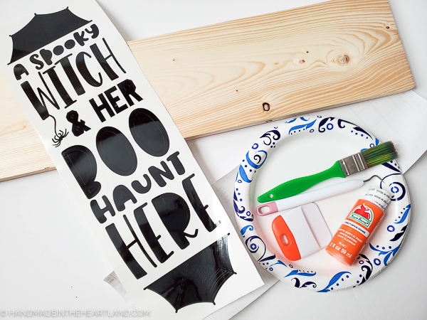 Supplies to make a wood painted Halloween sign with vinyl lettering