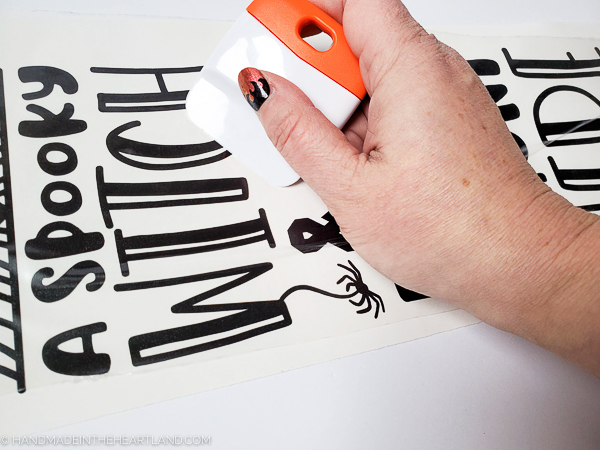 Using a spatula to transfer vinyl lettering