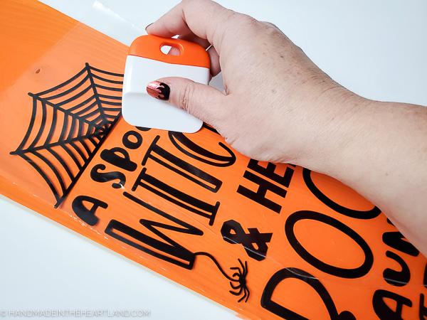 applying vinyl lettering to a diy halloween sign