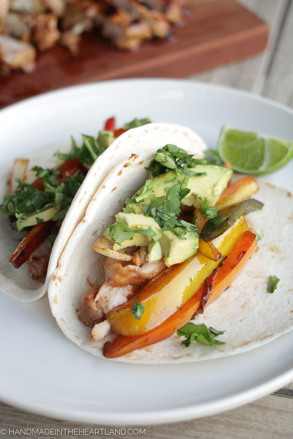 chicken and veggie fajitas tacos on white plate