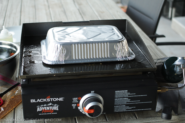 aluminum pan covering food cooking on a blackstone outdoor griddle