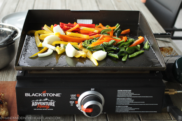 bell peppers, poblano peppers and onions cooking on a Blackstone griddle outside