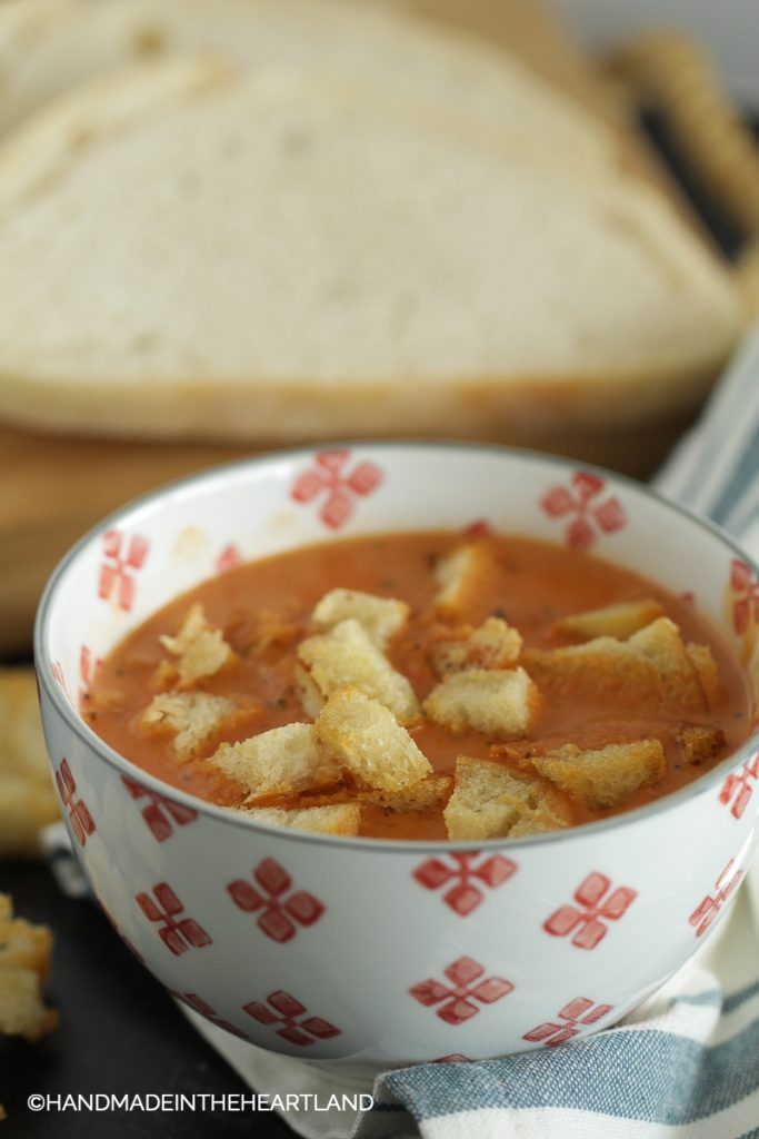 A bowl with tomato soup with croutons and sourdough bread in background
