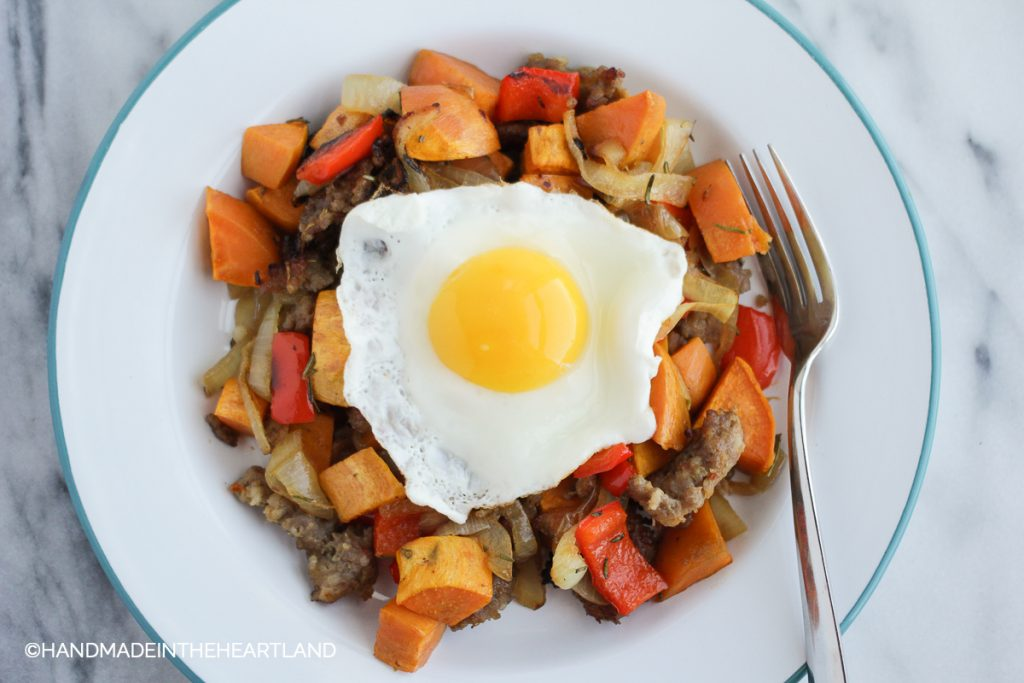 sausage, onions, bell peppers and sweet potatoes, roasted on a plate with sunny side egg on top