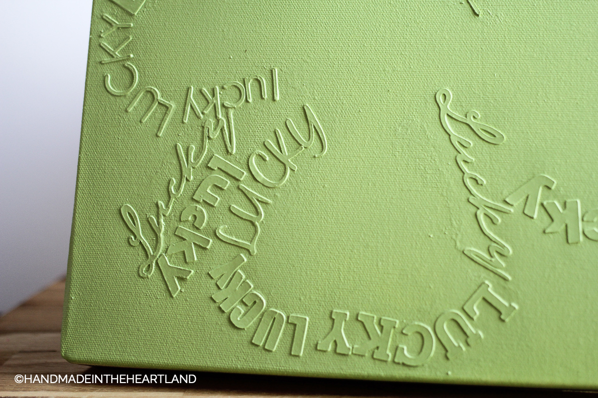 lucky words in different fonts on a canvas in the shape of a four leaf clover