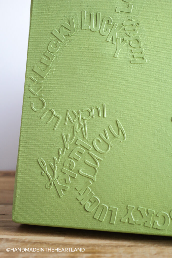 monochromatic green canvas with words Lucky in the shape of a 4 leaf clover
