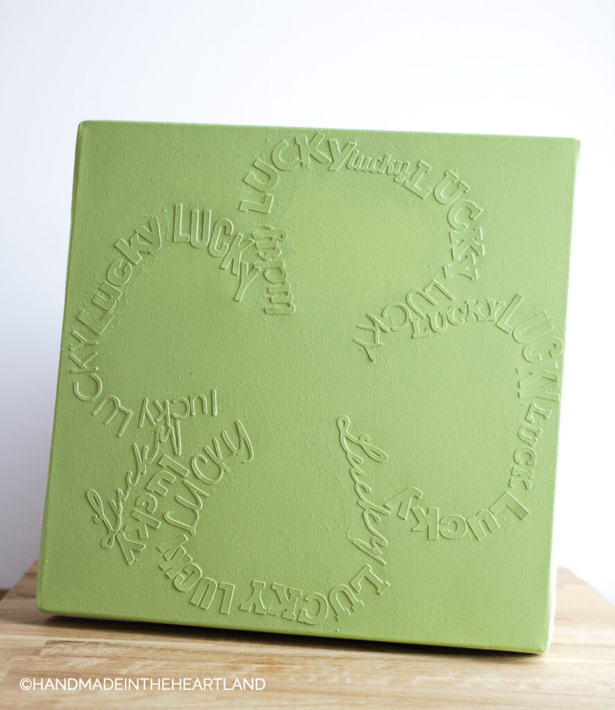 monochromatic green canvas with lucky writing in the shape of a 4 leaf clover