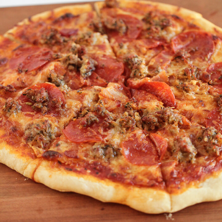 meat lovers pizza sitting on a wood cutting board sliced.