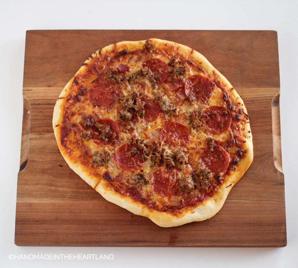 homemade pizza with pepperoni, sausage and bacon sitting on a wood cutting board