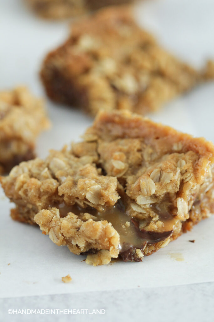 square of salty carmelita bars siting on parchment paper