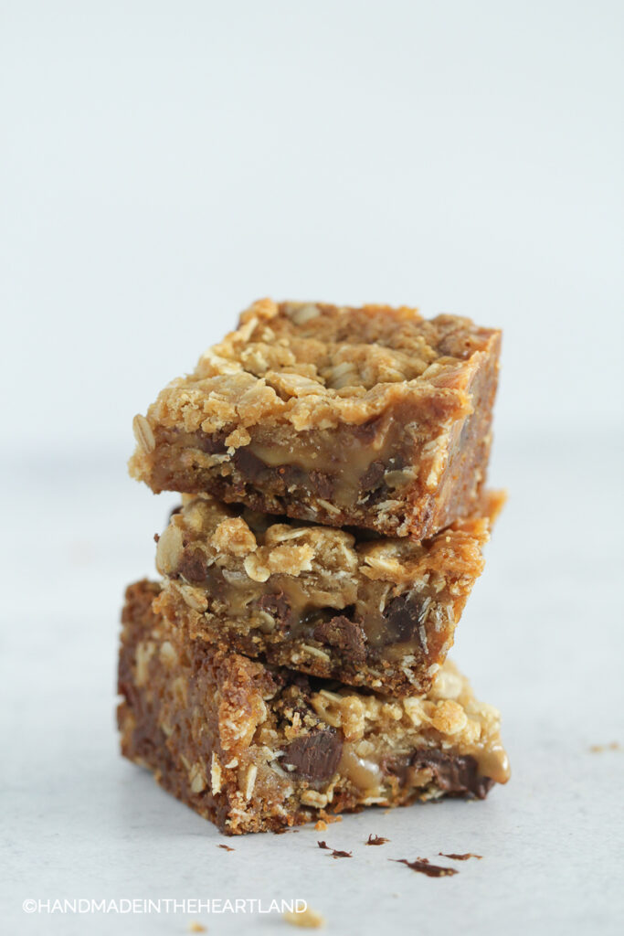 salty carmelita bars stacked on top of each other with white background