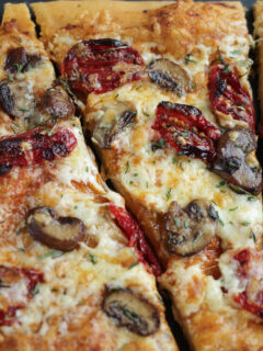 slice of pizza with mushrooms and sun-dried tomatoes