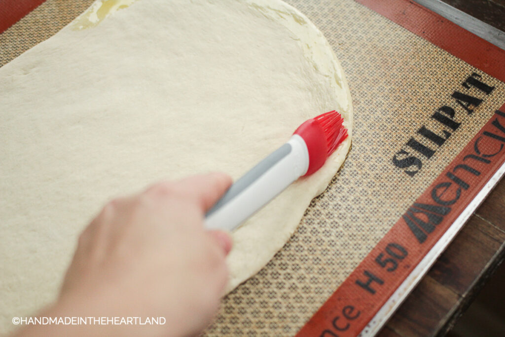brushing olive oil onto pizza crust with a silicone basting brush