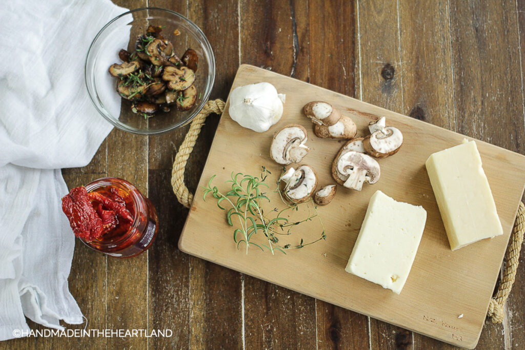 toppings for pizza with mushrooms, cheese, rosemary, sundried tomatoes sitting on wood board and wood table