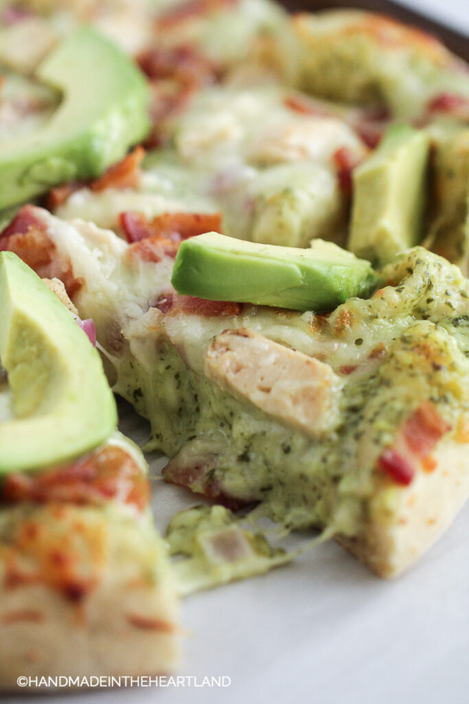 Pizza slice with melty cheese, chicken, and avocado on top