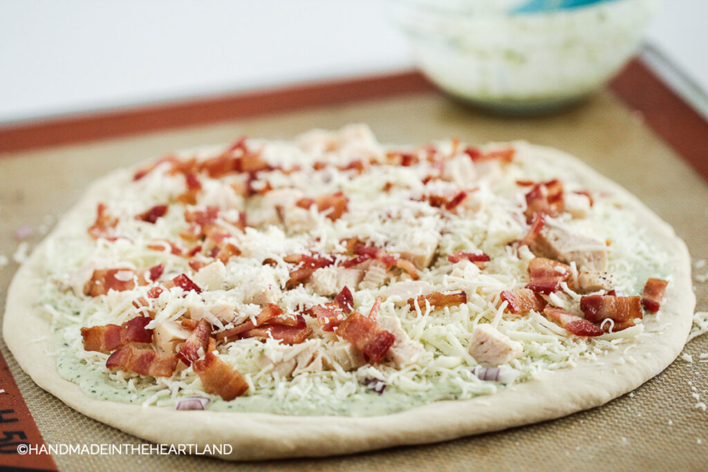 chicken bacon ranch pizza ready to be cooked sitting on a silpat nonstick baking liner