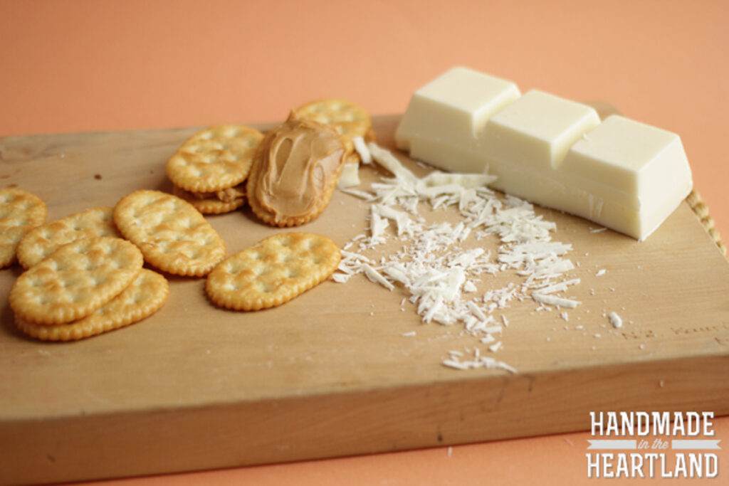 brick of vanilla almond bark and peanut butter spread on crackers sitting on a cutting board