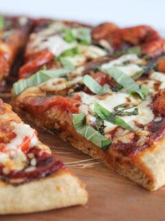 Homemade Caprese Pizza on wood cutting board