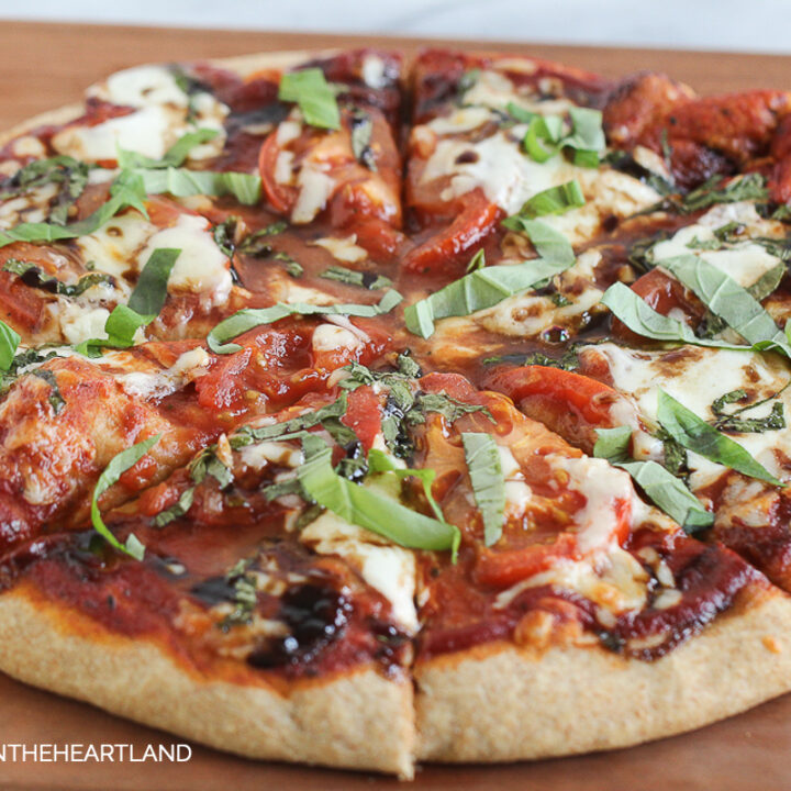 Circle Pizza with fresh mozzarella, basil and tomatoes with red sauce sitting on cutting board