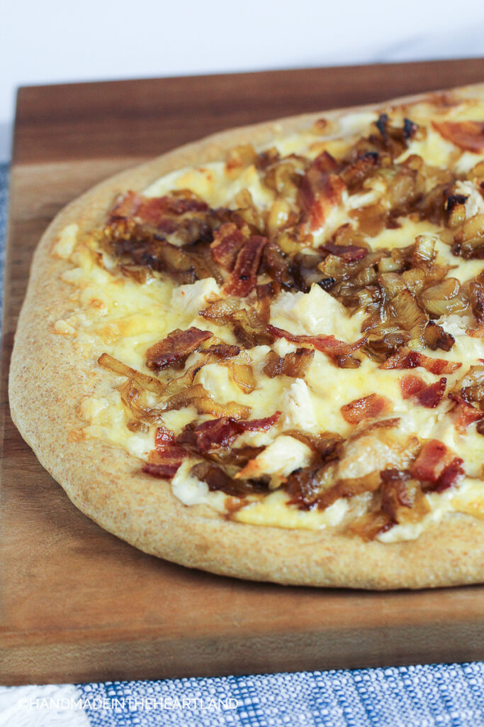 Homemade pizza with chicken, apples and caramelized onions sitting on a cutting board