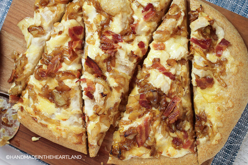 sliced homemade pizza with chicken, apples and caramelized onions